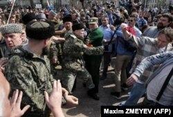 Людина в камуфляжній формі і папасі б'є учасника акції «Він нам не цар» у Москві 5 травня 2018 року