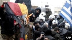 Greek demonstrators burn a German flag while trying to enter the parliament during an antiausterity protest in Athens.