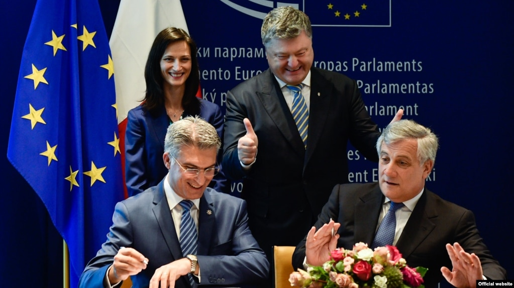 Ukrainian President Petro Poroshenko (top right) looks on as he attends the signing ceremony for a new visa-liberalization regime with the European Union in Strasbourg on May 17.