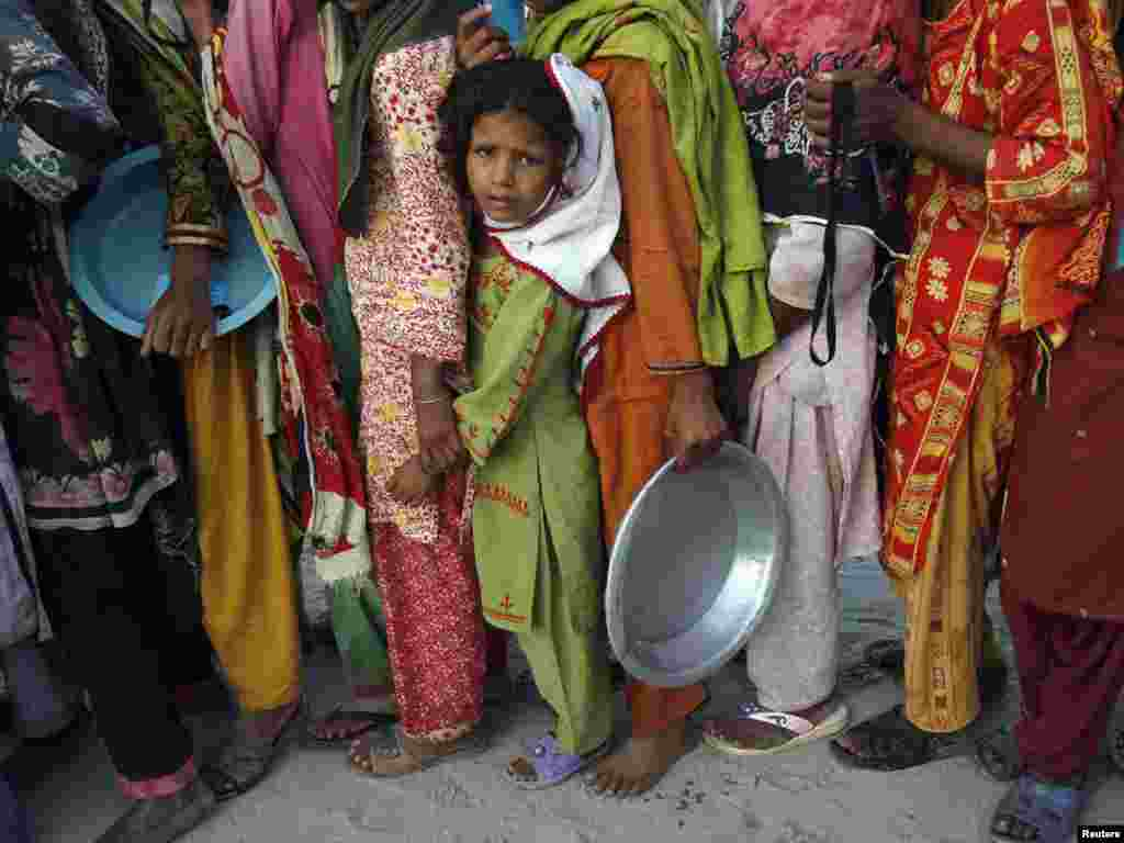 A flood victim stands in queue with others to get food handouts while taking refuge with her family in a relief camp for flood victims in Sukkur, in Pakistan's Sindh Province, on August 27. Photo by Athar Hussain for Reuters