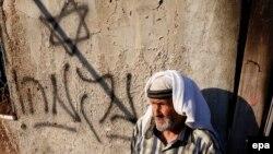 پیرمرد فلسطینی در کنار نوشتهای به زبان عبری به معنای «انتقام»