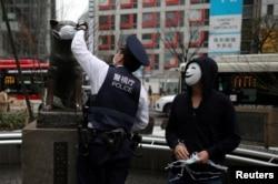 Полицейский символически надевает медицинскую маску на статую знаменитого японского пса Хатико, ставшего символом верности. Токио, 7 апреля 2020 года
