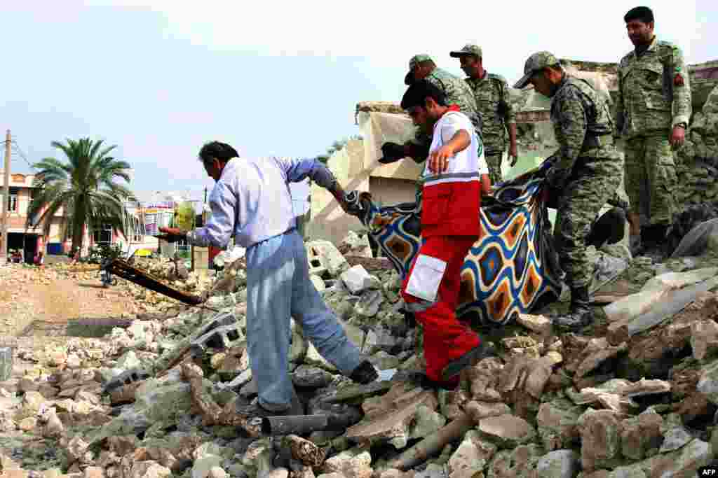 Soldiers and aid workers help a man carry his belongings salvaged from the rubble of his house in the town of Shonbeh, southeast of Bushehr, Iran, following a magnitude 6.3 earthquake. (AFP)