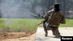 یکی از شبهنظامیان هوادار دولت مرکزی عراق در حال تیراندازی به نیروهای حکومت اسلامی در نزدیکی بغداد