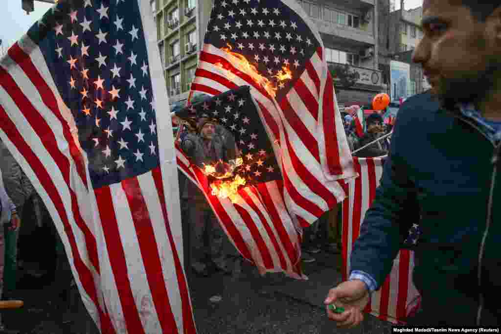 Iranians burn U.S. and Israeli flags in Tehran.