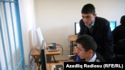 Students at a school in Azerbaijan peer at a computer monitor. (file photo)