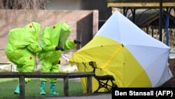 Members of the emergency services in green biohazard suits afix the tent over the bench on March 8 where a man and a woman were found on March 4 in critical condition in Salisbury.