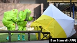 Investigators in green bio-hazard suits examine the site where Sergei Skripal and his daughter Yulia were found poisoned in Salisbury, England.