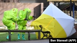 British emergency service workers in green biohazard suits place a the tent over the bench where Sergei Skripal and his daughter, Yulia, were found in critical condition on March 4.