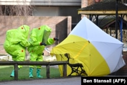 Investigators in green bio-hazard suits examine the site where Sergei Skripal and his daughter Yulia were found poisoned in Salisbury, England, earlier this year.