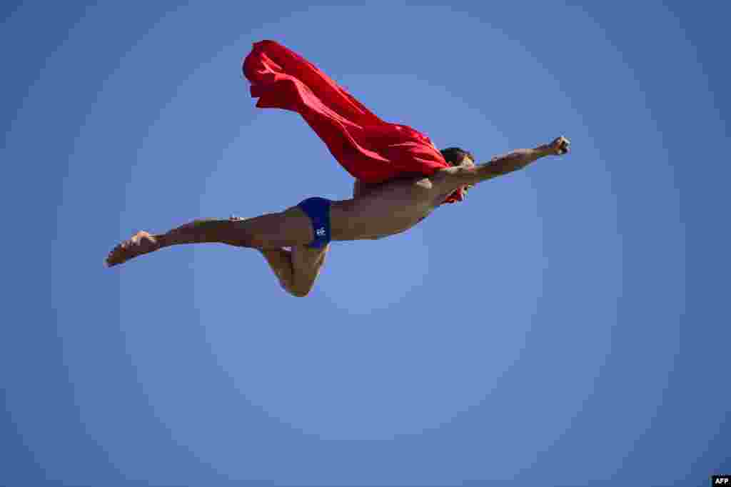 Czech Michal Navratil dives dressed as Superman after the men's high-diving final competition at the FINA World Championships in Barcelona. (AFP/Javier Soriano)