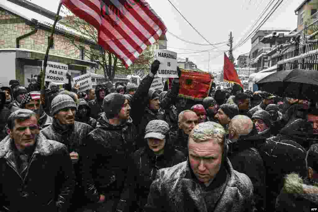 "Protesters hold a combined U.S. and Albanian flag and placards, including one reading ""Do Not Insult Kosovo,"" during a protest by Kosovar Albanians in front of the French Embassy in Pristina after Kosovo's former Prime Minister Ramush Haradinaj was arrested in France on January 4 in response to an international arrest warrant for war crimes filed by Serbia. (AFP/Armend Nimani)"