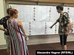 Дискуссия на избирательном участке рядом с информацией о лидерах партий