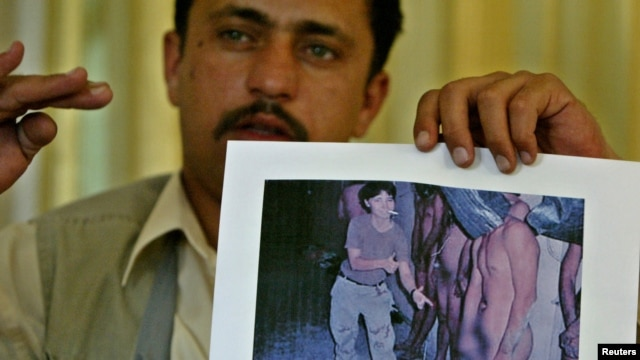 Saddam Saleh, a former prisoner at Abu Ghraib, shows a photograph at a 2004 press conference from the scandal that includes him in the middle of a group of naked prisoners being mocked by Lynndie England.