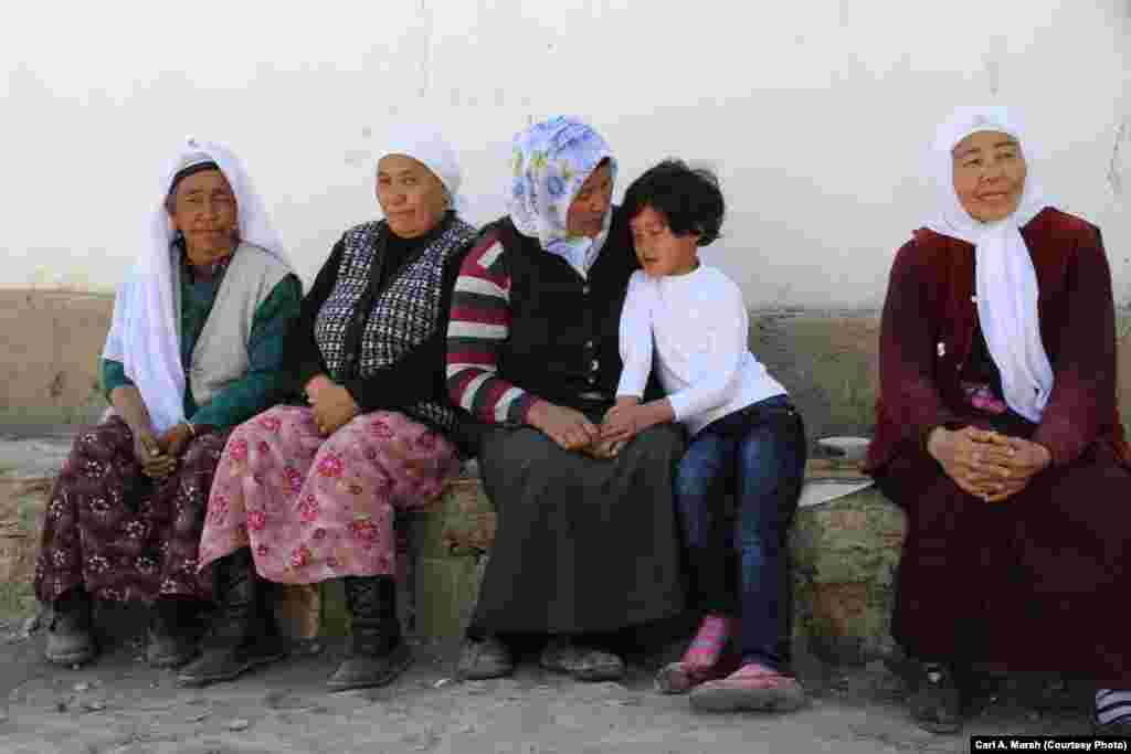 Women and a girl wait for a wedding party in eastern Turkey. Many Kyrgyz marry within their community, but those who go to Turkish universities often marry outsiders and don't return to the village. More young women than men receive a university education.