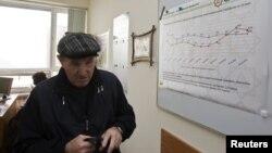 Жеке меншік жинақтаушы зейнетақы қорына келген зейнеткер ақпараттық тақтаның қасынан өтіп барады. Алматы, 24 қаңтар 2013 жыл.