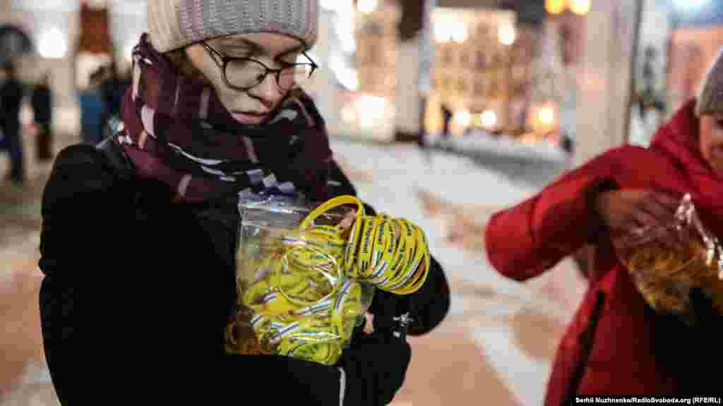 На акции раздавали браслеты с именами тех, кого незаконно удерживают в России. На другой стороне браслета надпись – «Крым – это Украина»