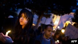 People hold candles during a demonstration on Bourguiba Avenue in central Tunis late on January 22.
