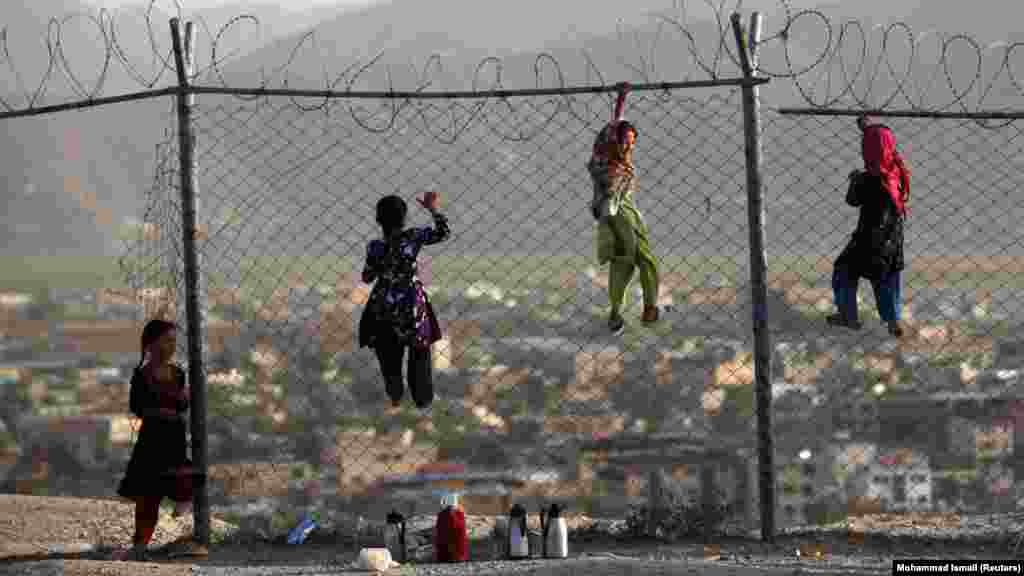 Afghan children climb onto a fence while playing as they sell tea in Kabul. (Reuters/Mohammad Ismail)