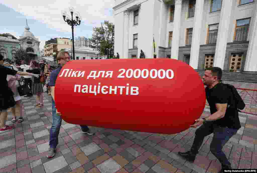 "Ukrainian activists carry a giant pill with the slogan, ""The Law 10313 is medicine for 2 million patients,"" during a protest in front of the parliament building in Kyiv. Activists rallied to demand that lawmakers accept a bill regulating the use of cannabis in medicine and scientific research. (epa-EFE/Sergei Dolzhenko)​"