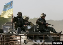 Members of the Ukrainian armed forces ride on an armored personnel carrier as they patrol area near Artemivsk in eastern Ukraine on June 4.
