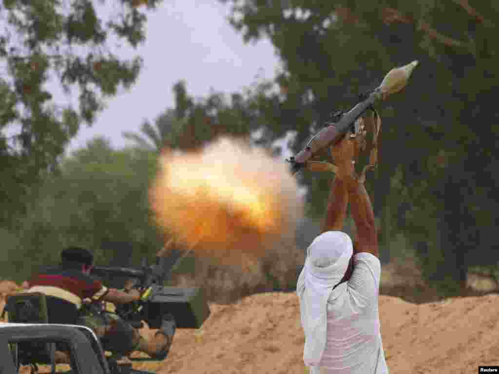 A fighter for Libya's anti-Qaddafi forces fires an RPG-7 during fighting in an area about 1 kilometer from the center of Sirte on October 3. (Photo by Anis Mili for Reuters)