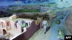 Сотрудник афганского музея идет рядом с экспонатами, изображающими войну афганцев против СССР. Герат, 27 апреля 2012 года.