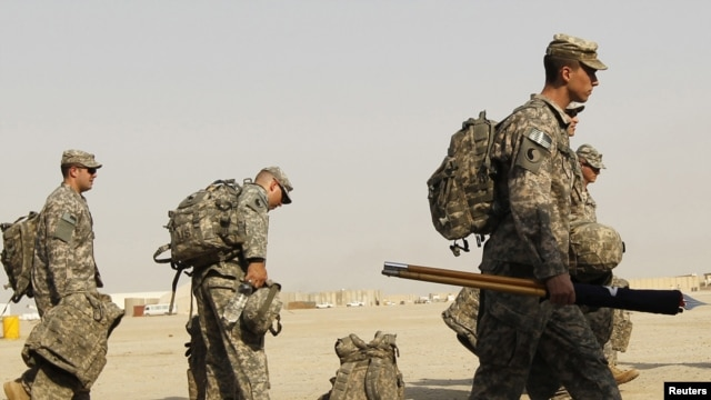 U.S. soldiers carry their luggage as they prepare to pull out of Iraq at Tallil Air Base near Nassiriya