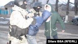 Сотрудники полицейского спецназа ведут молодого мужчину. Село Бурыл Жамбылской области, 17 февраля 2016 года.