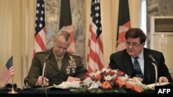 US commander in Afghanistan, General John Allen (left) and Afghan Defense Minister Abdul Rahim Wardak sign a security coordination agreement during a ceremony in Kabul on April 8.