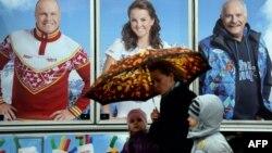 Женщина с детьми проходит рядом с рекламным щитом компании, продающей спортивную одежду с символикой Олимпиады.