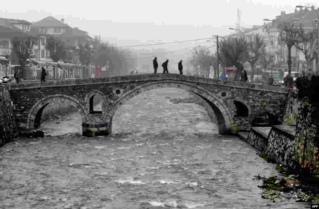 Pedestrians walk on the Old Stone Bridge during a cold and foggy morning in the town of Prizren, Kosovo. (AFP/Armend Nimani)
