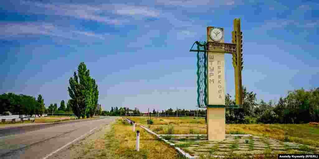 Стелла с рисовым колосом при въезде в село Ишунь со стороны Симферополя. Наверху в круге написано на украинском языке :«Асоціація «Виробники рису»