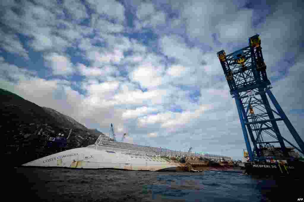 "One year after a tragic accident that left 32 people dead, the ""Costa Concordia"" cruise ship still lies aground off the Italian island of Isola del Giglio. (AFP/Filippo Monteforte)"