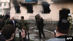 People use their mobile phones to take photos of the scene of a gunfight between Russian security forces and militants in the Chechen capital, Grozny, in April 2011.