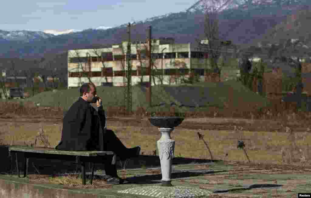 Local resident Vitaly Benia rests on a bench at an abandoned railway station in the town of Tkvarcheli.
