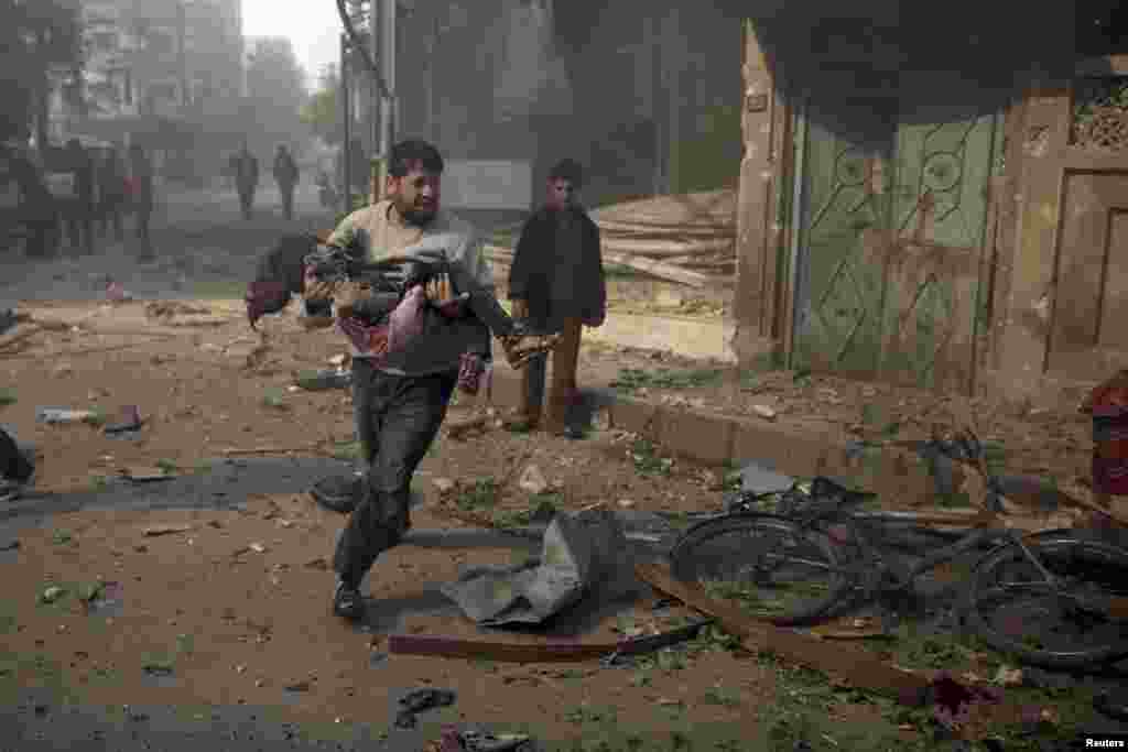 A man carries an injured girl from a site hit by what activists said were air strikes by forces loyal to Syria's President Bashar al-Assad, in the Douma neighborhood of Damascus on November 7.