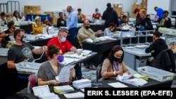 США - открепительные удостоверения обрабатываются и проверяются отделом регистрации и выборов округа Фултон в большом зале на State Farm Arena в Атланте, штат Джорджия, США, 4 ноября 2020 года.