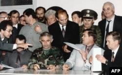 Александр Лебедь (за столом, второй справа) подписывает Хасавюртовские мирные соглашения с президентом Чечни Асланом Масхадовым. 30 августа 1996 года.
