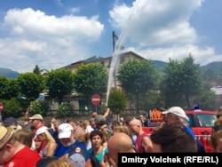 Пожарные поливают разгоряченных паломников