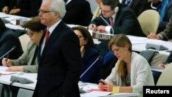 Постоянный представитель США при ООН Саманта Пауэр проверяет свой мобильный телефон, когда рядом проходит постопред России Виталий Чуркин