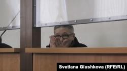 Подсудимый пастор Бахтжан Кашкумбаев улыбается приветствует свою жену перед началом суда. Астана, 13 февраля 2014 года.