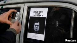"""Кулатылган президент Виктор Януковичтин """"өзгөчө коркунучтуу"""" деген сөз менен кошо унаанын айнегине чапталган сүрөтү. Киев, 24-февраль, 2014."""