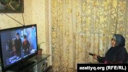 Жительница Алматы Мейрамгуль Саркулова смотрит у себя дома цифровое телевидение. 18 марта 2014 года.