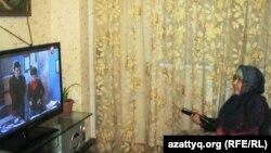 Мейрамгүл Сарқұлова теледидар қарап отыр.
