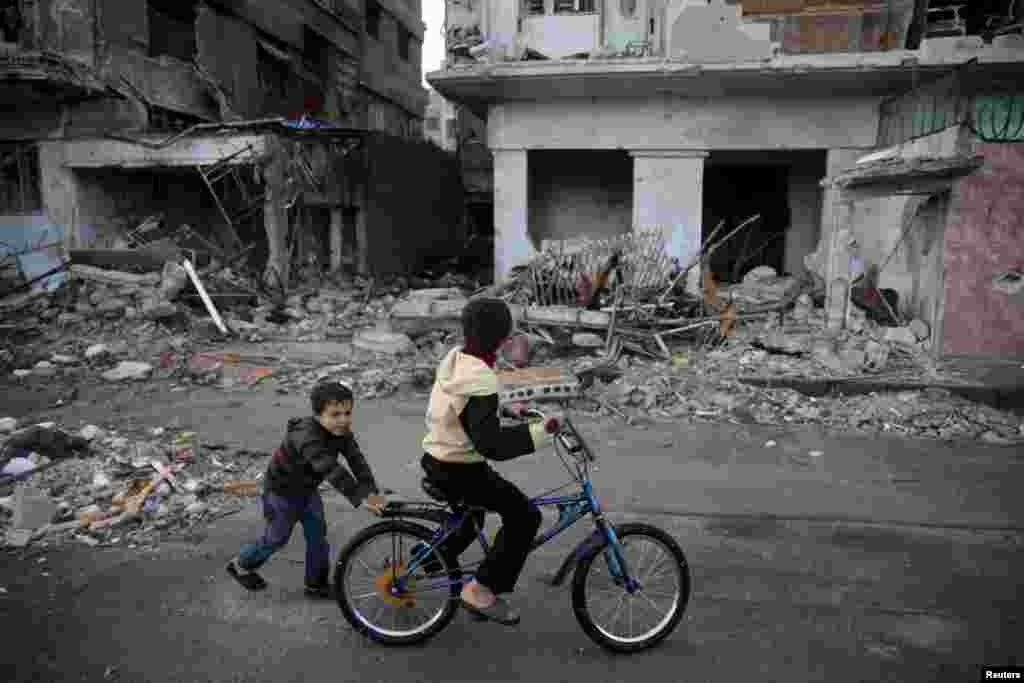 Children play on a bicycle among war-damaged buildings...