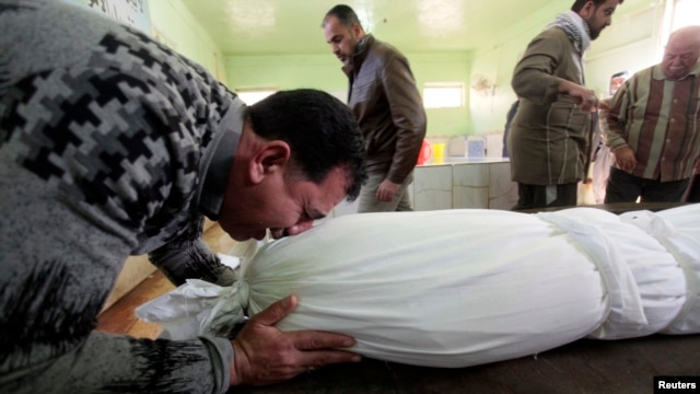 A man sobs over the shrouded body of his son, who was killed by a car-bomb attack, before his burial at a cemetery in Najaf, south of Baghdad, on January 31.