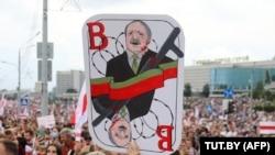 Минскиде митингчилердин бири кармап чыккан Лукашенконун шакаба сүрөтү.