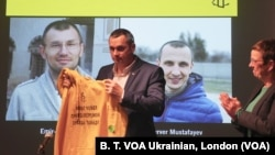 Oleg Sentsov ve Amnesty International Büyük Britaniya müdiri Kate Allen. Ekranda – Rusiyede mahkum etilgen Ukraina vatandaşları. Londra, 2019 senesi noyabrniñ 19-nda