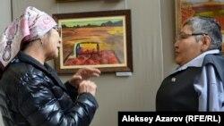 Кәріпбек Күйіков суреттері қойылған көрмеге келген адаммен әңгімелесіп тұр. Алматы, 18 қазан 2019 жыл.